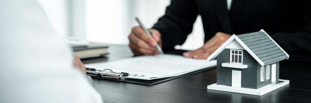 家に関連する書類に必要事項を記入している男性
